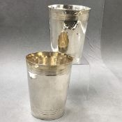 A PAIR OF SILVER BEAKERS, UNHALLMARKED, STAMPED ON BASES STERLING 925, WITH HAMMERED AND REEDED
