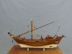 A SCALE MODEL TEAK DHOW WITH WHITE PAINTED KEEL AND BLACK AND WHITE TILLER HANDLE. W 105cms.