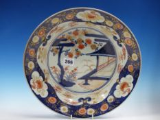 AN 18th C. JAPANESE IMARI DISH CENTRALLY PAINTED WITH A CHERRY TREE BLOSSOMING BY A PAVILION, THE