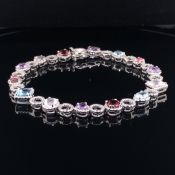 AN 18ct WHITE GOLD DIAMOND AND MULTI GEMSET BRACELET. INDIVIDUALLY DIAMOND HALO SET WITH FOURTEEN