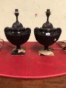 A PAIR OF BRONZE ROPE HANDLED COVERED URN TABLE LAMPS, THE SPIRALLY FLUTED BODIES ON SOCLES AND