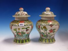 A PAIR OF CHINESE FAMILLE VERTE BALUSTER JARS AND COVERS, EACH PAINTED WITH TWO PANELS OF LOTUS ON A