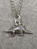 A SILVER DINOSAUR PENDANT SUSPENDED ON A SILVER 45cm CURB CHAIN.