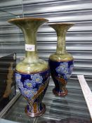 A PAIR OF ROYAL DOULTON POTTERY TALL VASES WITH FLARED RIMS AND FLOWER DECORATION.