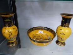 A CARLTON WARE YELLOW GROUND BOWL, AND A MATCHING PAIR OF VASES.