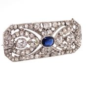 AN EDWARDIAN SAPPHIRE AND DIAMOND PANEL BROOCH. THE CENTRE OVAL MIXED CUT SAPPHIRE A MEDIUM TO