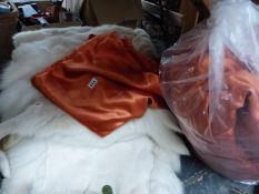 A SET OF RUSSET SILK BEDDING, AND TWO FUR RUGS.