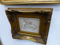 A DECORATIVE RELIEF PLAQUE OF WINGED PUTTI IN GILT FRAME