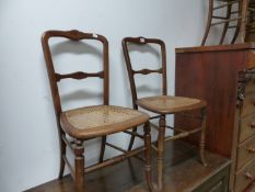A SET OF FOUR CHAIRS WITH STAR ROUNDELS INLAID INTO THE TOP RAILS ABOVE CANED BACKS AND SEATS