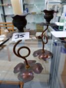 A PAIR OF ARTS AND CRAFTS COPPER CANDLESTICKS.