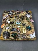 AN ASSORTED COLLECTION OF BROOCHES DISPLAYED ON A VINTAGE WOVEN CUSHION. TOTAL NUMBER OF BROOCHES