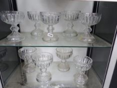 A SET OF NINE CUT GLASS GOBLET SHAPED VASES WITH HOLLOW FEET