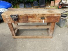 A WORK BENCH WITH MOUNTED VICE