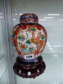 A JAPANESE IMARI JAR, COVER AND WOODEN STAND