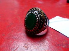 A GENTS OVAL CUT GREEN GEMSTONE SIGNET RING IN A CARVED SILVER BLACK AND GILDED HEAVY MOUNT.