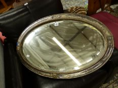 AN OVAL BEVELLED GLASS MIRROR IN SILVER PLATED FRAME