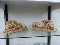 A PAIR OF CAST CERAMIC RECLINING LIONS