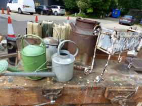 A SMALL MILK CHURN, 3 GALVANISED WATERING CANS AND A RECTANGULAR PLANTER IN A PAINTED WROUGHT IRON