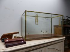 A GLAZED BRASS TABLE TOP DISPLAY CASE, A WOODEN CANNON, TWO CASES OF WINE SERVING IMPLEMENTS AND