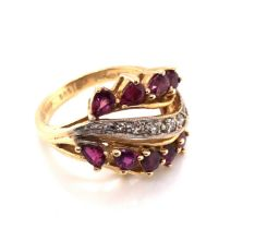 A RUBY AND DIAMOND DRESS RING. TEN PEAR CUT RUBIES FRAME A GRAIN SET WAVE OF DIAMONDS. APPROX RUBY