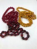 THREE ROWS OF UNTESTED BEADS CONSISTING OF TWO RED STRANDS AND ONE AMBER COLOURED STRAND. (THE AMBER
