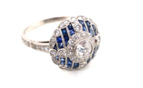 AN EDWARDIAN STYLE DARK CORNFLOWER BLUE SAPPHIRE AND OLD CUT DIAMOND DOMED CLUSTER RING. THE CENTRAL