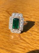 AN ART DECO EMERALD AND DIAMOND PANEL RING. THE LOZENGE SHAPE EMERALD APPROX 11 X 6mm, SURROUNDED BY