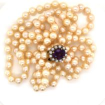 A MATINEE DOUBLE ROW OF CREAM COLOURED KNOTTED CULTURED PEARLS ON A 9ct STAMPED GOLD CLASP SET