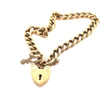 A 9ct HALLMARKED GOLD CURB BRACELET COMPLETE WITH SAFETY CHAIN AND PADLOCK CLASP. THE BRACELET