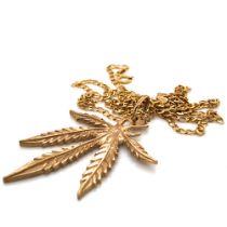 A 9ct GOLD HALLMARKED MARIJUANA PENDANT SUSPENDED ON A 9ct HALLMARKED GOLD CURB CHAIN. PENDANT