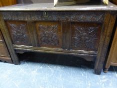 AN OAK COFFER, THE THREE FRONT PANELS CARVED WITH FOLIAGE QUATREFOILS. W 118 x D 50 x H 72cms.