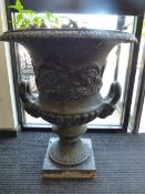 A PAIR OF CAST IRON VICTORIAN URNS, THE TWO HANDLES WITH MASK TERMINALS ABOVE FLUTED SOCLES AND SQUA