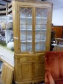 A 19TH CENTURY GLAZED PINE CORNER CUPBOARD, THE TOP WITH FOUR WHITE PAINTED SHELVES ABOVE A DRAWER A