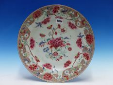 AN 18th C. CHINESE FAMILLE ROSE DISH PAINTED WITH FLOWERS WITHIN A SHAPED RED AMMONITE SCROLL RIM