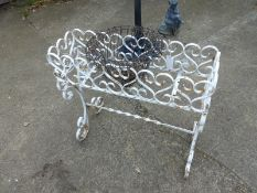 A PAINTED IRON PLANT STAND AND A WIREWORK HANGING BASKET.