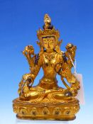 A TIBETAN GILT METAL FIGURE OF THE WHITE TARA SEATED ON A LOTUS THRONE, HER FACE AND HAIR WITH