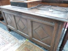 AN ANTIQUE OAK COFFER, THE THREE DIAMOND CENTRED PANELS TO THE FRONT ENCLOSED BY CHIP CARVED BANDS.