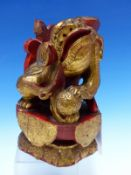 A CHINESE CARVED WOOD LION SEATED WITH A BROCADE BALL PARCEL GILT ON A RED LACQUER GROUND. H 23cms.