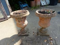 A PAIR OF COMPOSITE CLASSICAL STYLE GARDEN URNS.