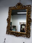 A FLORENTINE RECTANGULAR MIRROR IN FOLIATE PIERCED GILT FRAME, THE SIDES CENTRED BY SHELLS, THE