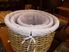 A GRADED SET OF THREE MAUVE TEXTILE LINED CYLINDRICAL BASKETS