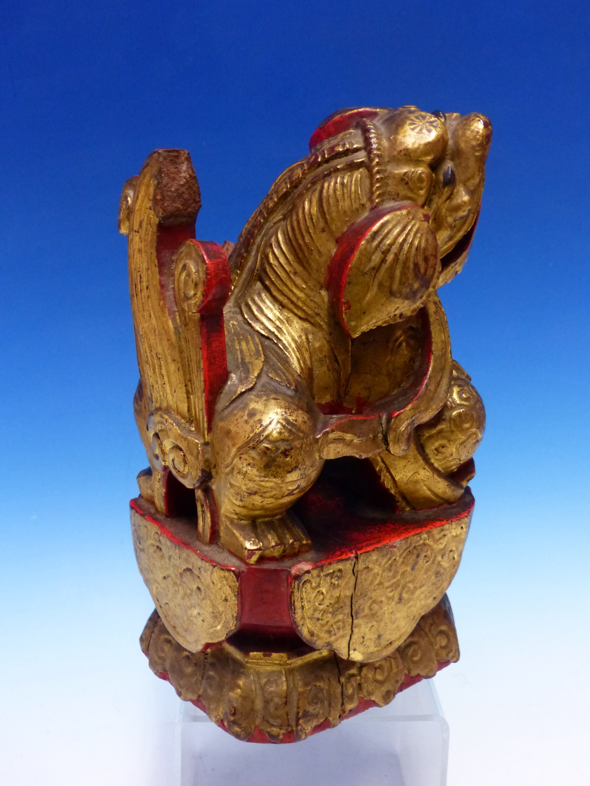 A CHINESE CARVED WOOD LION SEATED WITH A BROCADE BALL PARCEL GILT ON A RED LACQUER GROUND. H 23cms. - Image 2 of 5