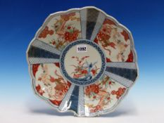 A JAPANESE IMARI DISH, THE BARBED RIM OUTSIDE RADIATING PANELS FEATURING GILT LIONS BY TEMPLES AND I