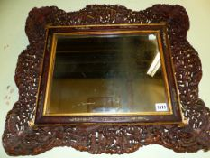 A CHINESE RECTANGULAR MIRROR, THE WOODEN WAVY EDGED FRAME PIERCED AND CARVED WITH BATS AT THE CORNE