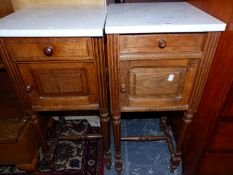 A PAIR OF FRENCH WHITE MARBLE TOPPED OAK BEDSIDE CUPBOARDS ON REEDED TAPERING CYLINDRICAL LEGS, EACH