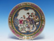 A CHINESE STYLE RUBY BACKED DISH PAINTED WITH TWO LADIES AND TWO CHILDREN WATCHING A CAT