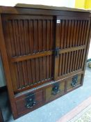 A CHINESE HARDWOOD SIDE CABINET WITH TWO BLIND SLATTED DOORS ENCLOSING SHELVES OVER THREE DRAWERS. W