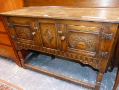 AN OAK SIDE BOARD, THE TWO DOORS CARVED WITH A ROUND ARCH MOTIFS, THE TURNED LEGS JOINED BY A