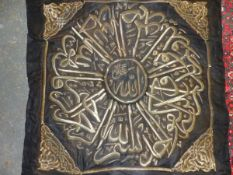 A BLACK SILK HANGING WORKED IN GOLD THREAD WITH A SQUARE OF FOLIAGE ENCLOSING AN ISLAMIC INSCRIBED