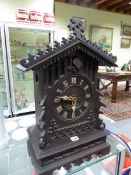 A STAINED WOOD GOTHIC ORNAMENTED TWO TRAIN CUCKOO CLOCK STRIKING ON A COILED ROD. H 58cms.